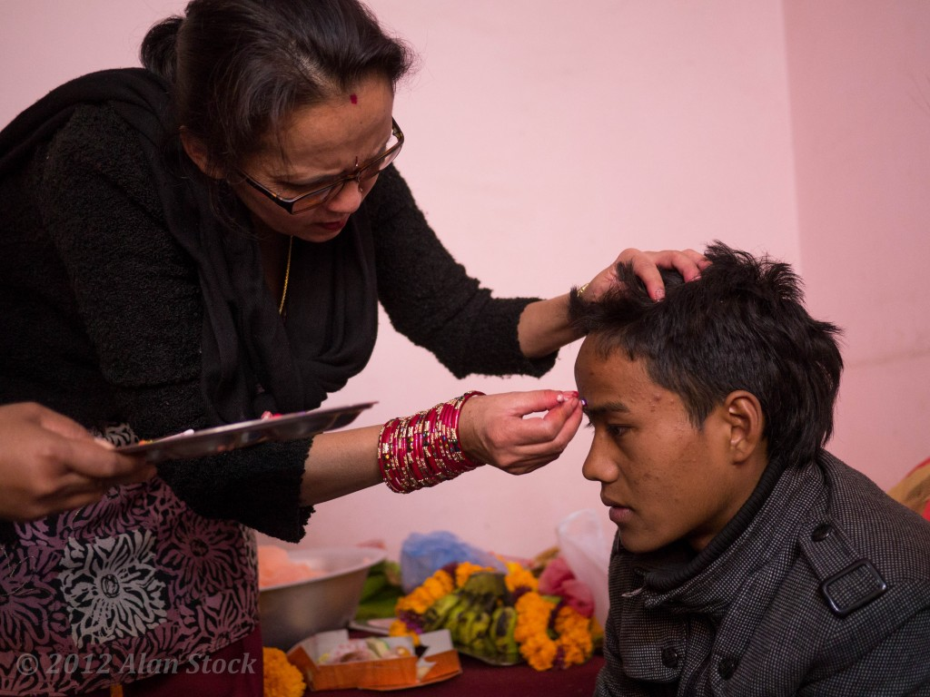 The aunt carefully dots the tikka line on her son's forehead.
