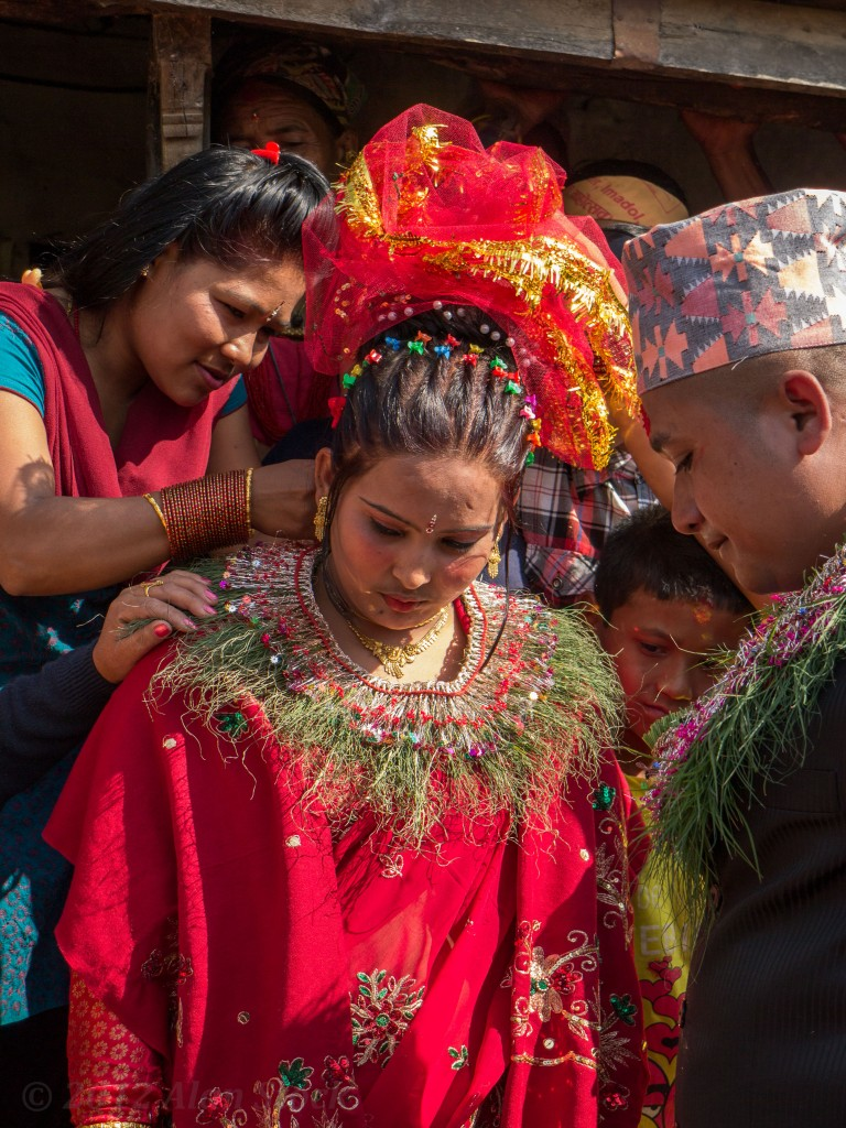 A grass garland is affixed around the bride's neck