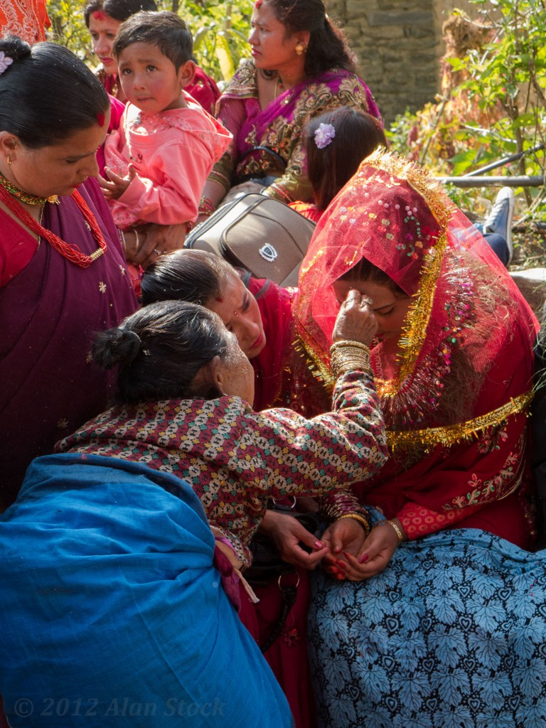 An old lady gives the bride a tika